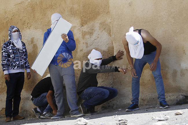 Palestinians youths take cover during clashes with Israeli security forces on April 25, 2015 in Al-Tur neighbourhood of annexed Arab east Jerusalem, after Israeli police shot dead a knife-wielding Palestinian who attempted to stab colleagues at an east Jerusalem checkpoint. The 17-year-old assailant from Al-Tur managed to get past one checkpoint but was brought down at a second near Al-Zaim without any police casualties, a spokeswoman said. Photo by Saeb Awad