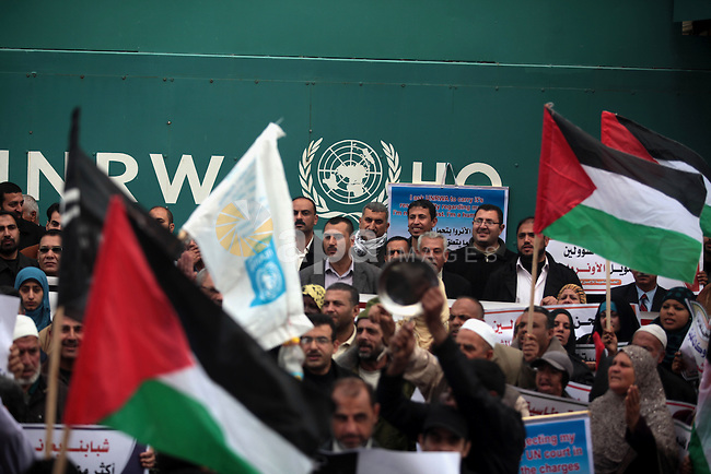 Palestinians take part in a protest against the decision made by the United Nations Relief and Works Agency (UNRWA) to reduce food aid delivered to the Gaza Strip in front of the UNRWA headquarters in Gaza City on March 16, 2014. Photo by Ashraf Amra