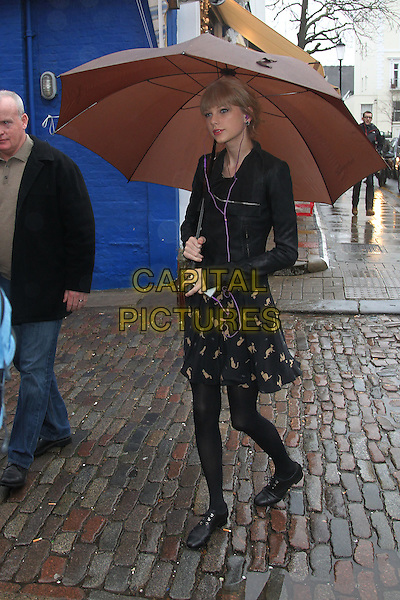 Taylor Swift in Bond Street and Notting Hill, London, England..January 24th, 2012.full length black tights jacket leather scarf knitted grey gray umbrella cat cats animal print dress skirt.CAP/HIL.©John Hillcoat/Capital Pictures .