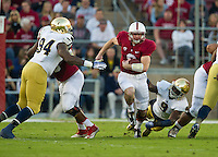 Stanford Cardinal quarterback Kevin Hogan (8) carries the ball as Notre Dame Fighting Irish linebacker Jaylon Smith (9) attempts to tackle.