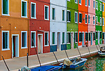 A row of colourful houses on a canal on the island of Burano in the Venetian Lagoon in Italy.
