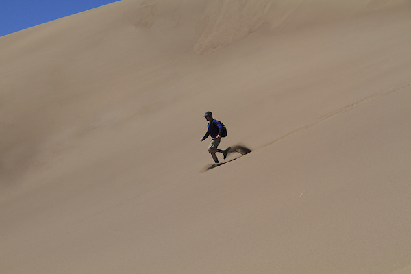 Man running downhill in Great Sand Dunes National Park, Colorado John offers private photo trips to Great Sand Dunes National Park and all of Colorado. All year long.