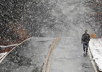 A pedestrian walks along West Queen Street near the Clemson University campus during a snow shower on Tuesday. Forecasters are calling for several more inches of snow to fall on the Upstate in the coming days.