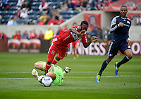 New England goalkeeper Matt Reis (1), who made an unsuccessful attempt to get the ball, trips Chicago forward Patrick Nyarko (14) for a penalty kick.  The Chicago Fire defeated the New England Revolution 3-2 at Toyota Park in Bridgeview, IL on Sept. 25, 2011.