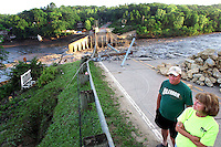 "Carl and Elaine Burkle of Dyersville survey the damage near the breached dam at Lake Delhi early Sunday morning, July 25, 2010.  ""It just makes you sick.  Our kids grew up on this lake, such a shame."" said Elaine, who has siblings with cabins on the lake.  Flood water breached and destroyed the dam the day before, emptying the nine mile long lake."