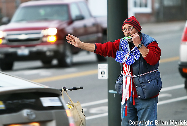 "Street artist Jeff Cornell stands at the corner of Water Street and Third Ave. in Ellensburg in an effort to encourage citizens to vote, Thursday, Oct. 25, 2012.  ""I'm drawing attention to the right thing to do.  It's called vote,"" Cornell said while waving at passing traffic and occasionally playing a note or two on a plastic harmonica.  ""I believe everybody should go out and do something, even if it's wrong."" (Brian Myrick / Daily Record)"