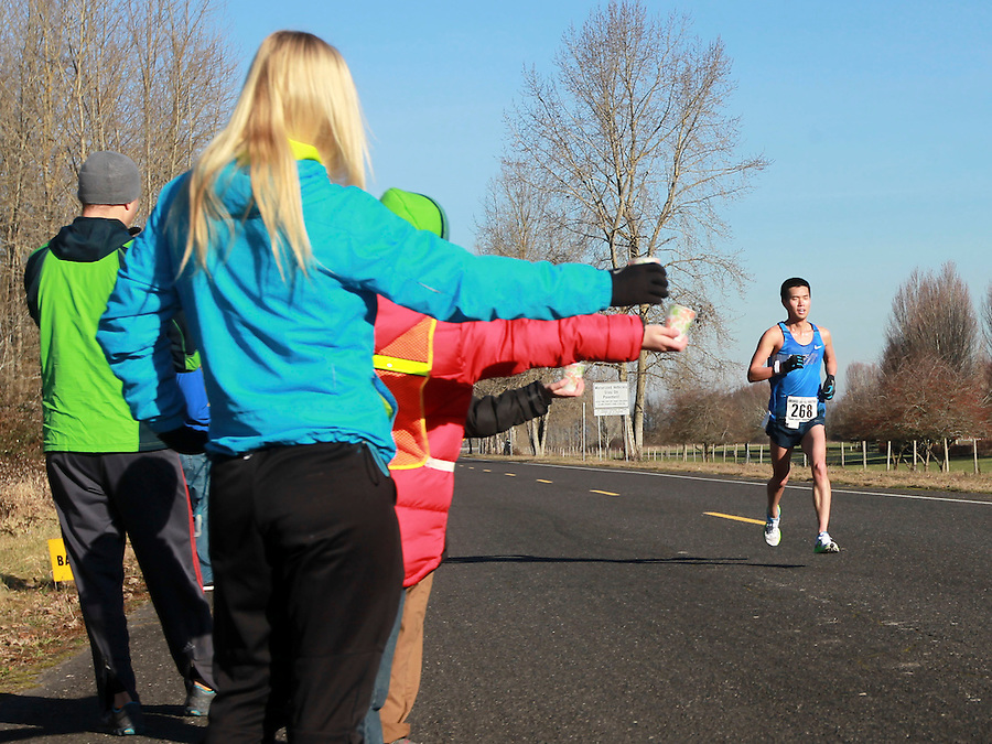 Volunteers offer water to runner Johnson Lee as he passes in the annual Vancouver Lake Half Marathon Sunday January 26, 2014. (Natalie Behring/for the Columbian)