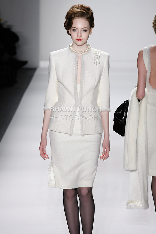 """Model walks runway in an ivory wool boucle princess skirt suit seamed w/mink-chain-mink stole, from the Zang Toi Fall 2012 """"Glamour At Gstaad"""" collection, during Mercedes-Benz Fashion Week New York Fall 2012 at Lincoln Center."""