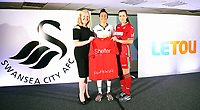 Pictured: Katy Hosford (RED) and Alicia Powe (WHITE) of the Swansea City FC Ladies' team model the home and away kits with Shelter Cymru representative. Monday 19 June 2017<br />