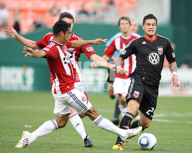 Santino Quaranta #25 of D.C. United moves the ball away from Michael Umana #4 and Ben Zemanski #21 of Chivas USA during an MLS match at RFK Stadium, on May 29 2010 in Washington DC. United won 3-2.