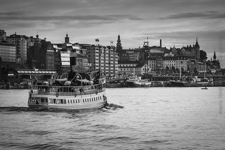 Ångbåten Norrskär i sommarskymningen mellan Södermalm och Slussen i Stockholm i svartvitt.