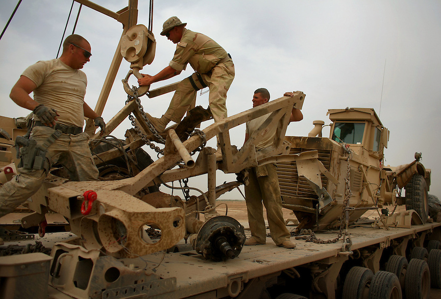 """A retrieval crew lashes down the wreckage of a """"Husky"""" IED detecting engineering vehicle damaged when its front-end was sheared away by an IED strike on the outskirts of Baqubah, Iraq on Sunday May 27, 2007. The Husky - with its V-shaped hull and articulated construction is designed to come apart when struck by an IED rather than absorbing the blast as do flat-bottomed vehicles like Bradleys and Humvees."""