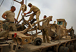 "A retrieval crew lashes down the wreckage of a ""Husky"" IED detecting engineering vehicle damaged when its front-end was sheared away by an IED strike on the outskirts of Baqubah, Iraq on Sunday May 27, 2007. The Husky - with its V-shaped hull and articulated construction is designed to come apart when struck by an IED rather than absorbing the blast as do flat-bottomed vehicles like Bradleys and Humvees."