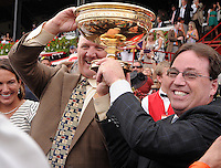 Trainers Kenny McPeak and Kiaran McLaughlin hoist the shared trophy after their horses Golden Ticket and Alpha deadheaded to share the Travers Stakes win at Saratoga Race Course on Travers Stakes Day  in Saratoga Springs, New York on August 25, 2012.