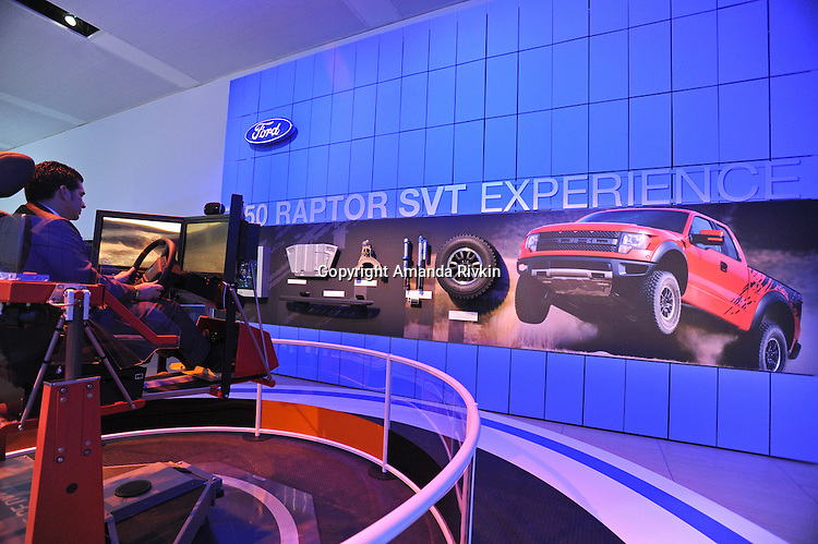 A man sits in a simulation vehicle which mimics the experience of driving a Ford Raptor at the Detroit Auto Show in Detroit, Michigan on January 11, 2009.