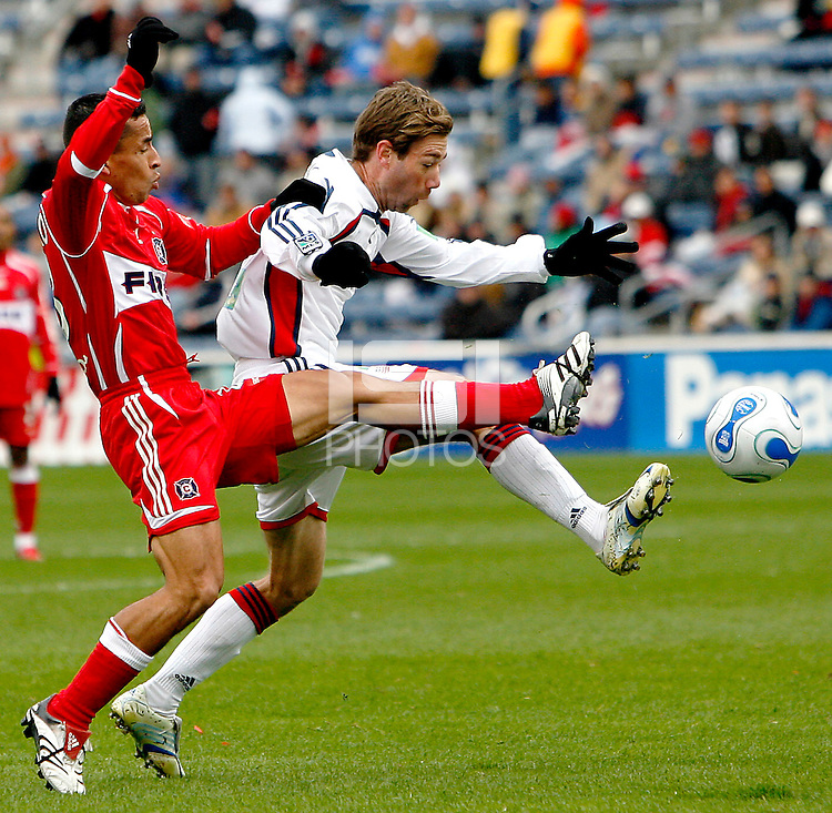 Chicago Fire midfielder Ivan Guerrero (23) and New England Revolution midfielder Steve Ralston (14) lunge for a loose ball.  The Chicago Fire defeated the New England Revolution 1-0 in the first game of their playoff series at Toyota Park in Bridgeview, IL on October 22, 2006..