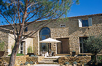 Contemporary windows in the stone facade of this property in south-west France open onto a sun-drenched terrace
