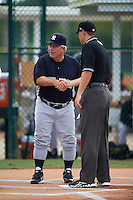 GCL Yankees manager Marc Bombard shakes hands with umpire Conner Colhane after the lineup exchange before the second game of a doubleheader against the GCL Pirates on July 31, 2015 at the Pirate City in Bradenton, Florida.  The game was suspended after two innings due to rain.  (Mike Janes/Four Seam Images)