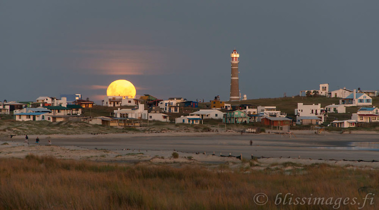 A rising full moon makes a dramatic appearance over sandy Cabo Polonio with its beautiful lighthouse and exotic community of cottages and bohemian shacks -Uruguay, East coast.