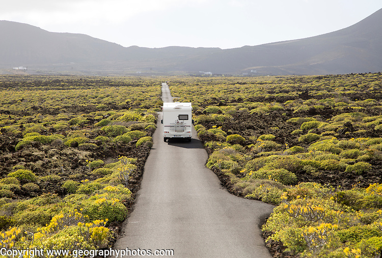 Motorhome on straight sealed tarmac road crossing lava flows Malpais de Corona, Lanzarote, Canary Islands, Spain