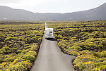 Motorhome on straight sealed tarmac road crossing lava flows Malpais de Corona, Lanzarote, Canary Islands, Spain