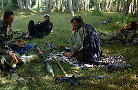 A commander and foot soldiers from the Wardak Mobile Patrol Unit discuss their next operation under the shade of a garden in a safe haven property