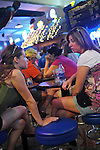 Women sit on stools at a bar with live music at the Minnesota State Fair in Saint Paul, Minnesota on August 30, 2008.