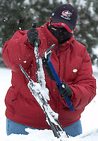 Lisa Rubinow uses an ice scraper to knock ice of the windshield wipers of her car as she prepares to go to work in Westerville, Ohio, Thursday, December 23, 2004. A winter storm covered central Ohio with as much as a foot of snow and an inch of ice forcing school and business closings.