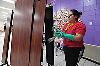 Lizzeth Solis ((CQ)), custodian at Walker Elementary School in Springdale, disinfects cafeteria tables Monday March 16, 2020 to help stop the spread of the corona COVID 19 virus. Meals are being served to students at several locations in Springdale. Visit nwaonline.com/200317Daily/ for more images. (NWA Democrat-Gazette/J.T. Wampler)