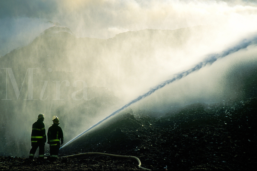 Fire fighters with hose.