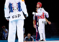 04 DEC 2011 - LONDON, GBR - Aaron Cook (GBR) (on right, in red) celebrates beating Nicolas Garcia (ESP) (on left, in blue) during their men's -80kg category semi final contest at the London International Taekwondo Invitational and 2012 Olympic Games test event at the ExCel Exhibition Centre in London, Great Britain .(PHOTO (C) NIGEL FARROW)