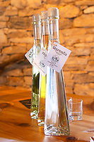Bottles of rakija grappa type spirit clear and with herbs. Glasses on a wooden table top. Triangular conic bottles with light shining through. Translucent. Toreta Vinarija Winery in Smokvica village on Korcula island. Vinarija Toreta Winery, Smokvica town. Peljesac peninsula. Dalmatian Coast, Croatia, Europe.