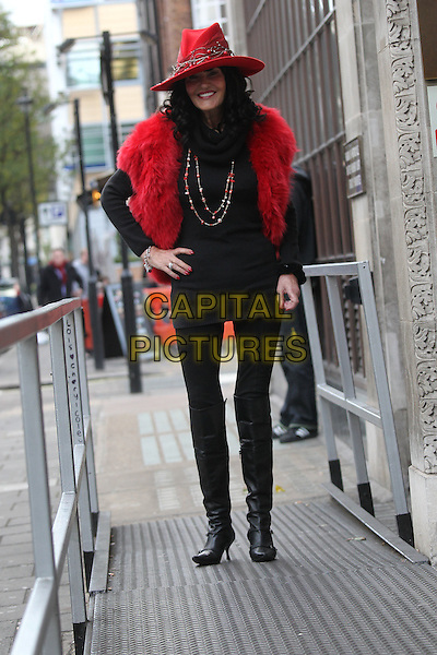 Hilary Devey arriving at  the studios of BBC Radio 1, London, England..December 7th, 2011.full length black red top leggings boots jacket hat fur furry necklace hand on hip.CAP/HIL.©John Hillcoat/Capital Pictures .