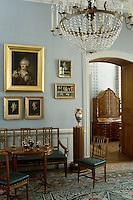 A series of gilt-framed paintings and portraits hang above a brass inlaid canape and matching table and chairs in this anteroom