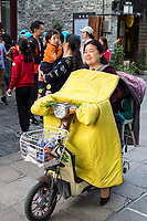 Yangzhou, Jiangsu, China.  Middle-aged Woman on her Electric Motorbike.