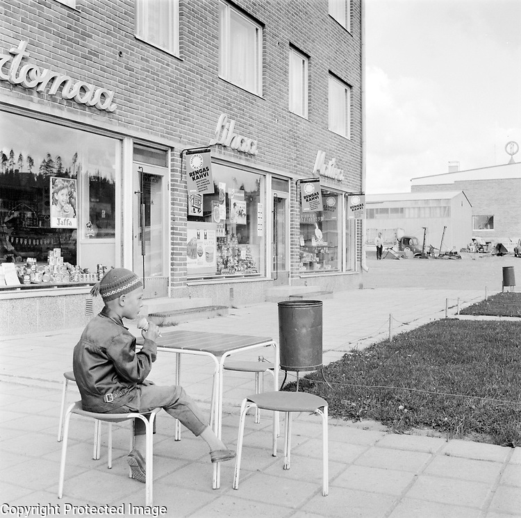Boy eating ice cream otide nwely constructed shops, Finland 1963