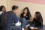 High school students talking and socializing in corridor during lunch break.