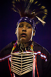 A young man in Northern Plains regalia awaits the next song during a noncompetitive, intertribal round of dancing after sunset.