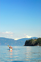 Male paddler in yellow kayak and red PFD paddling in San Juan Islands with Mount Baker visible in background, Sea Kayaking the San Juan Islands, WA.