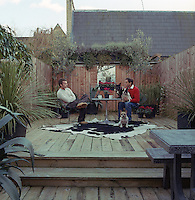 Ben de Lisi sitting on the right and his boyfriend Gerardo Vidaurre in the decked garden of their London home