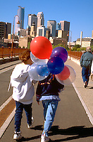 Friends age 10 walking across bridge with balloons at Exchange Charities Youth Festival.  Minneapolis  Minnesota USA