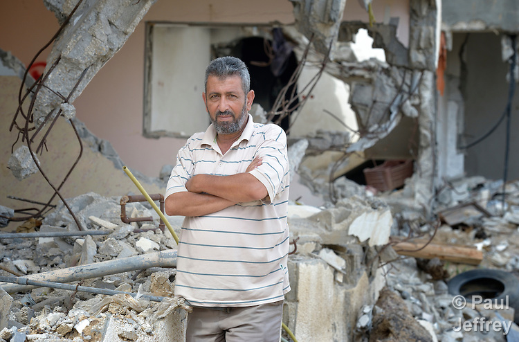 Abed Rabu Abu Jowe'a stands in front of the ruins of what was one his home in Khan Yunis, Gaza. Houses in the area were destroyed by Israeli air strikes during the 2014 war between the state of Israel and the Hamas government of Gaza.