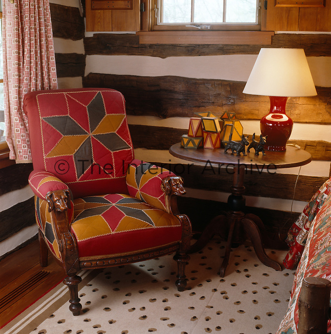 A patchwork armchair in a corner of this log-cabin style bedroom