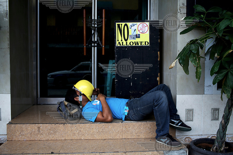 A labourer sleeps on the steps of a restaurant, beside a sign prohibiting the carrying of weapons within.