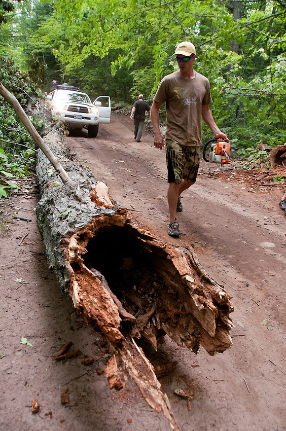Organizer Tom Dolaskie IV uses a chainsaw to trim a large tree fallen across a road during the 2010 U.P. Overland trip in the Upper Peninsula of Michigan.