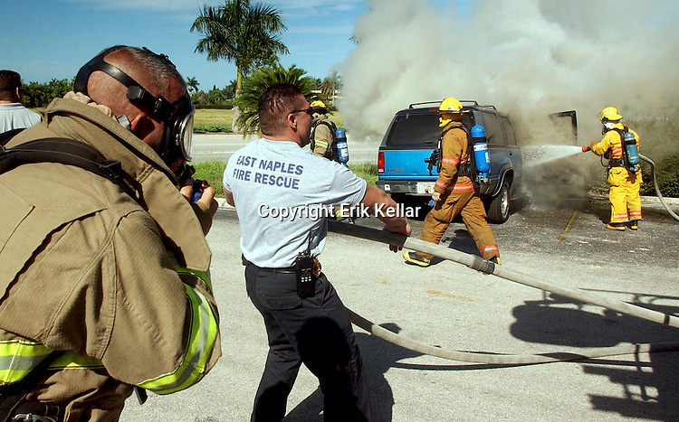 "Kitt Holland, 18, of Naples, stands next to what is left of his 1992 Ford Explorer, trying to reach his parents after East Naples Fire Department extinguishes a fire that engulfed the engine of his car in a parking lot between U.S. 41 and Davis Boulevard in Naples on Thursday morning. Holland, a student at International College majoring in computer technologies, was on his way to purchase a new car when smoke began to come from under his car's hood. After he pulled over, the car burst into flames. ""I don't think I'll get much of a trade-in now,"" Holland said. ""I even still have the Auto Shopper still on my front seat."" Holland, who works for Naples Technologies, plans on taking the weekend to continue to look for a new car. Erik Kellar/Staff .ek Avid Perez, left, a firefighter with East Naples Fire Department, suits up to fight a blaze that engulfs a 1992 Ford Explorer owned by Kitt Holland in Naples on Thursday morning. The cause of the fire is being blamed on engine mechanical failure according to Lt. John Obst of the East Naples Fire Department."