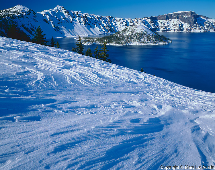 Crater Lake National Park, OR <br /> Wind sculpted snow patterns on the bluff above Eagle Cove with Wizard Island and the West Rim of Crater Lake in the distance