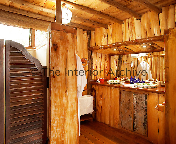 The bathroom of a boutique style luxurious wooden treehouse, made entirely of wood and grass. The interior has a rustic feel, with the talents of regional artists adding many of the finishing touches.