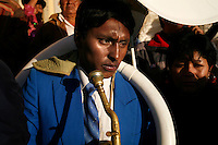 A band member with their instrument arrives at a church at dawn at the Carnaval de Oruro. During the fiesta many people sacrifice llamas and give offerings such as coca leaves and cigarettes to show their dedication to the Devil, a Virgin, Pachamama or Mother Earth. The Devil (or Uncle) is a mythical character that protects the miners of Oruro who work in dangerous conditions hundreds of metres below the ground. During the carnival, people dress in outrageous costumes and dance for days before arriving at the Church of Socavon, where they pay their respects to a virgin. Ironically, many of the dancers wear devil costumes.
