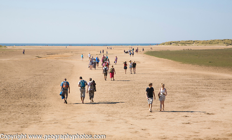 People walking across wide sandy beach at Holkham, north Norfolk coast, England